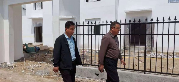 东明县焦园乡党委书记张建国(右)和包村干部一起到村台社区检查督导。